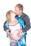 Pregnant woman kissing with man isolate. Young pregnant woman kissing with husband isolated on white Royalty Free Stock Images