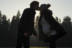 Pregnant woman kissing partner outdoors Royalty Free Stock Photography
