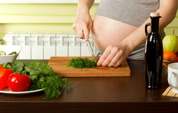 Pregnant woman on kitchen Stock Image