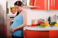 Pregnant woman in kitchen stock photos