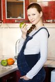 Pregnant woman at kitchen with apple Royalty Free Stock Photos