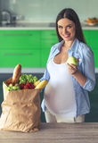 Pregnant woman in the kitchen royalty free stock images