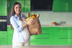 Pregnant woman in the kitchen. Beautiful pregnant woman is holding a paper bag with food, looking at camera and smiling while standing in her kitchen at home Royalty Free Stock Photos