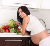 Pregnant woman in kitchen Stock Images