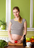 Pregnant woman on kitchen cooking Stock Photography
