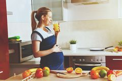 Pregnant woman on kitchen drinking fruit juice stock photography