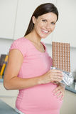 Pregnant woman in kitchen with large chocolate bar Stock Photos
