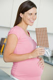 Pregnant woman in kitchen with large chocolate bar Royalty Free Stock Photo