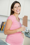 Pregnant woman in kitchen with large chocolate bar Royalty Free Stock Image