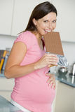 Pregnant woman in kitchen with large chocolate bar Stock Photo