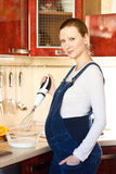 Pregnant woman in kitchen making a food and smilin Royalty Free Stock Image