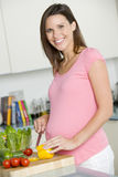 Pregnant woman in kitchen making a salad Stock Images