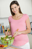 Pregnant woman in kitchen making a salad Royalty Free Stock Photos