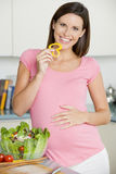 Pregnant woman in kitchen making a salad Stock Photo