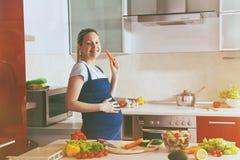 Pregnant woman on kitchen making salad Royalty Free Stock Photo