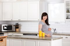 Pregnant Woman in Kitchen stock photos