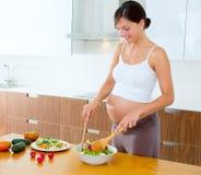 Pregnant woman at kitchen preparing salad Stock Image
