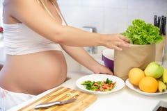 Pregnant woman at kitchen preparing salad, close up Stock Photo