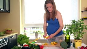 Pregnant woman at kitchen preparing salad stock video footage