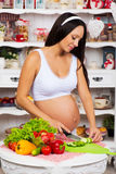 Pregnant woman in the kitchen preparing a vegetable salad. Healthy nutritious. Stock Image
