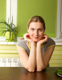 Pregnant woman on kitchen smiles on camera Stock Photo