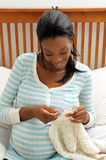 Pregnant Woman Knitting. Pregnant young African American woman knitting