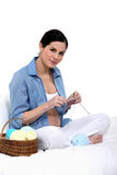 Pregnant woman knitting Stock Image