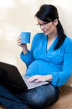 Pregnant woman and laptop Stock Photography