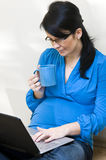 Pregnant woman and laptop Stock Image