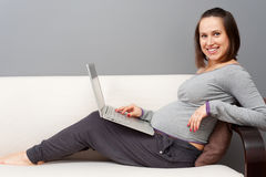 Pregnant woman with laptop at home. Smiley pregnant woman with laptop at home stock photography