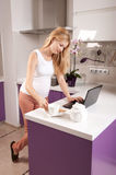 Pregnant woman with laptop in kitchen Royalty Free Stock Photo