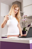 Pregnant woman with laptop in kitchen Stock Images