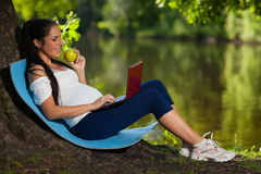 Pregnant  woman with laptop in the park. Stock Photos