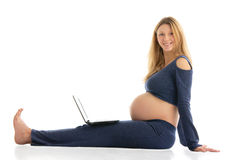 Pregnant woman with a laptop sitting on the floor Royalty Free Stock Image