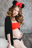 Pregnant woman with a large red-and-black bow. Stock Image