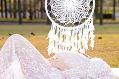 Pregnant woman laying down in field with macrame hanging mandala. Pregnant woman in white lace dress, laying down in field with macrame hanging mandala in stock photos
