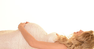 Pregnant woman laying down. Profile of young pregnant woman lying on her back holding her baby bump wearing white dress stock photos