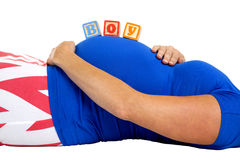 Pregnant woman laying down with wood blocks spelling boy on her Stock Photos