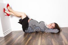 Pregnant woman laying on the floor Stock Photography