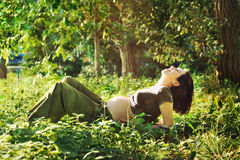 Pregnant woman laying on grass in park. Royalty Free Stock Photography
