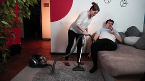 Pregnant woman with lazy husband is cleaning carpet with vacuum cleaner