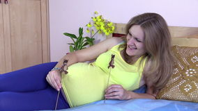 Pregnant woman lie on bed and play with small bear toys stock video footage