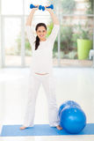Pregnant woman lifting dumbbells Royalty Free Stock Image