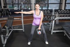 Pregnant woman lifting kettlebell stock images