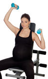 Pregnant woman lifting weights in the gym Royalty Free Stock Photos