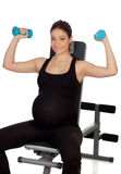 Pregnant woman lifting weights in the gym Royalty Free Stock Images