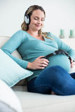 Pregnant woman listening to music with headphones on belly Royalty Free Stock Image