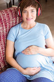 Pregnant woman listening to music Stock Photo