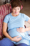 Pregnant woman listening to music Royalty Free Stock Images