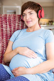 Pregnant woman listening to music Stock Image